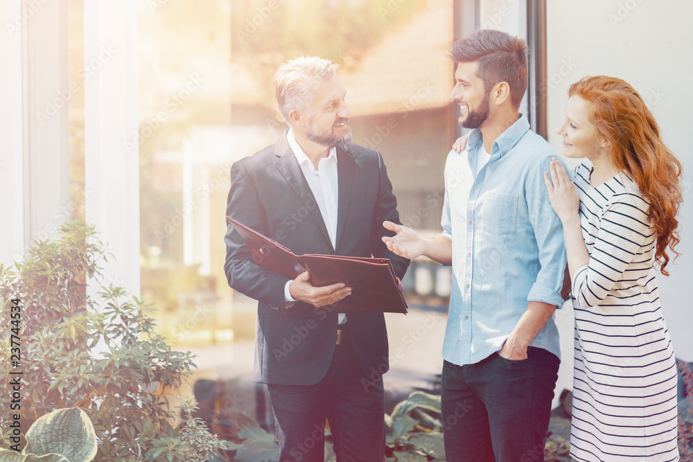Fototapeta Smiling couple talking with financial advisor about house loan