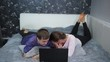 Young couple using a laptop lying on the bed. Something scary shows the screen