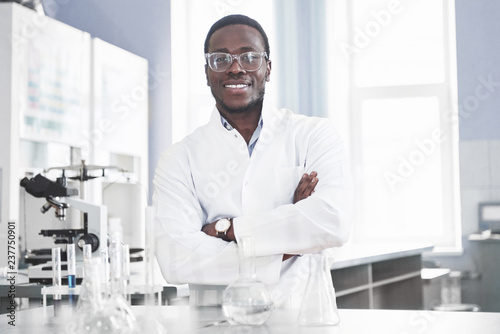 Fotografiet The scientist works with a microscope in a laboratory conducting experiments and formulas