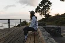 Female Skateboarder Sitting On...