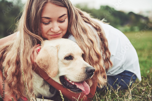 Frame with a beautiful girl with a beautiful dog in a park on green grass Wallpaper Mural