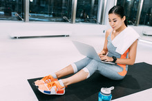Attractive Asian Girl With Towel On Shoulders Sitting On Fitness Mat And Typing On Laptop Keyboard At Gym