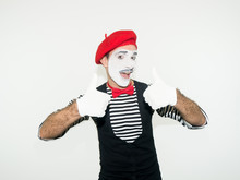 Happy Mime Showing Thumbs Up. Cheerful Behavior And Broad Smile Of A Male Actor During The Pantomime Show. Isolated On White.