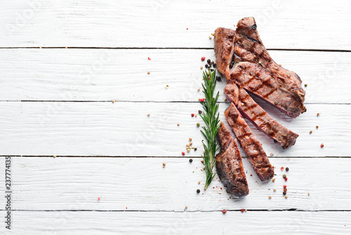Veal steak on a bone on a white wooden background. Free space for your text. Top view.