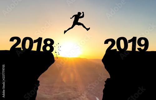 Photographie  Mann spring über Abgrund vor Sonnenuntergang mit der Beschriftung 2018/2019