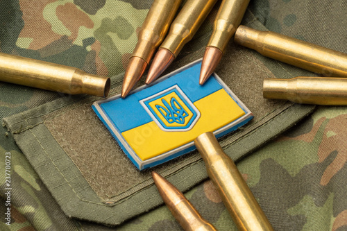 Ukrainian flag on the background of a camouflage military jacket and combat bullets Canvas Print