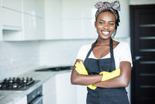 Smiling African American Housewife In Apron With Arms Crossed Cleaning At Home
