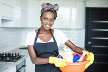 Smiling Young African Woman Holding Basket With Cleaning Equipment At Hause