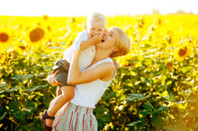 Portrait Of Mother And Her Cute Child Laughting In Sunflower Surroundings