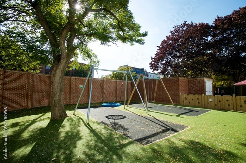 Photo Modern safe playground with a large swing rubber mat and astroturf in an enclosed yard on a sunny day