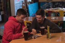 Friends Discussing On Mobile Phone At Table