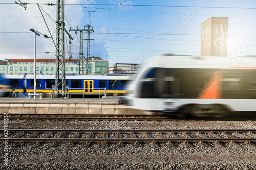 Obraz Fahrende Züge mit Häusern und Stromleitungen im Hintergrund - fototapety do salonu