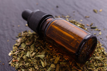 dried tarragon and essential oil on a dark stone background