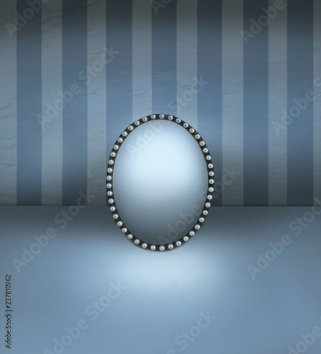 Ingelijste posters Surrealisme Small mirror with vintage frame decorated in pearls resting on a floor and with striped wall background