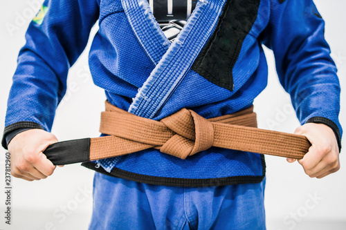 Midsection of a man in Brazilian Jiu Jitsu Gi holding the brown belt