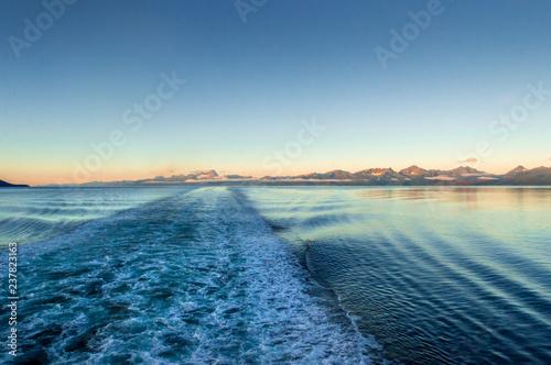 Fotografie, Obraz  Ship wake at dawn, lighting rugged mountains across ocean channel