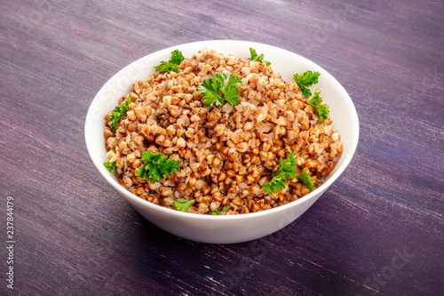 Fotografía  Cooked buckwheat in a bowl, garnished with fresh parsley, on a purple background