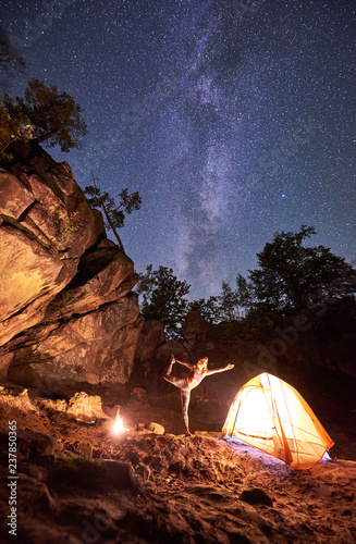 Foto op Aluminium Draken Campsite at night amid huge steep mountain rock formations. Attractive young woman doing yoga exercises at tourist tent on clear dark blue starry sky background. Tourism and sport concept. Narajasana