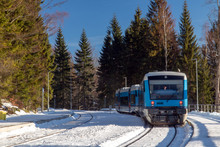 The Snowy Railway Station With Modern Train In The Mountains. The Empty Platform With Regional Train In The Winter Nature. Harrachov, Mountains Krkonose, Czech Republic.