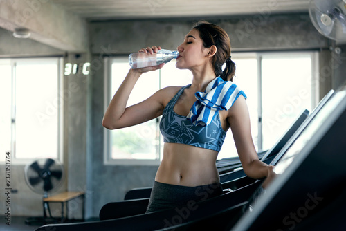 Fototapeta asian women thirsty drinking water after exercise in fitness gym