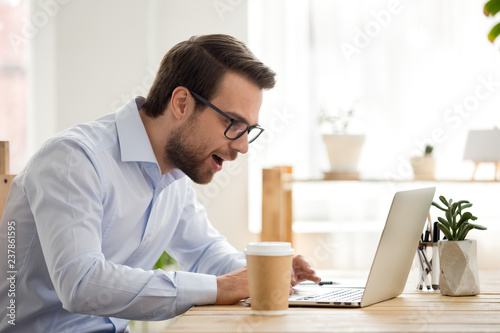 Excited male worker look at laptop screen reading breaking