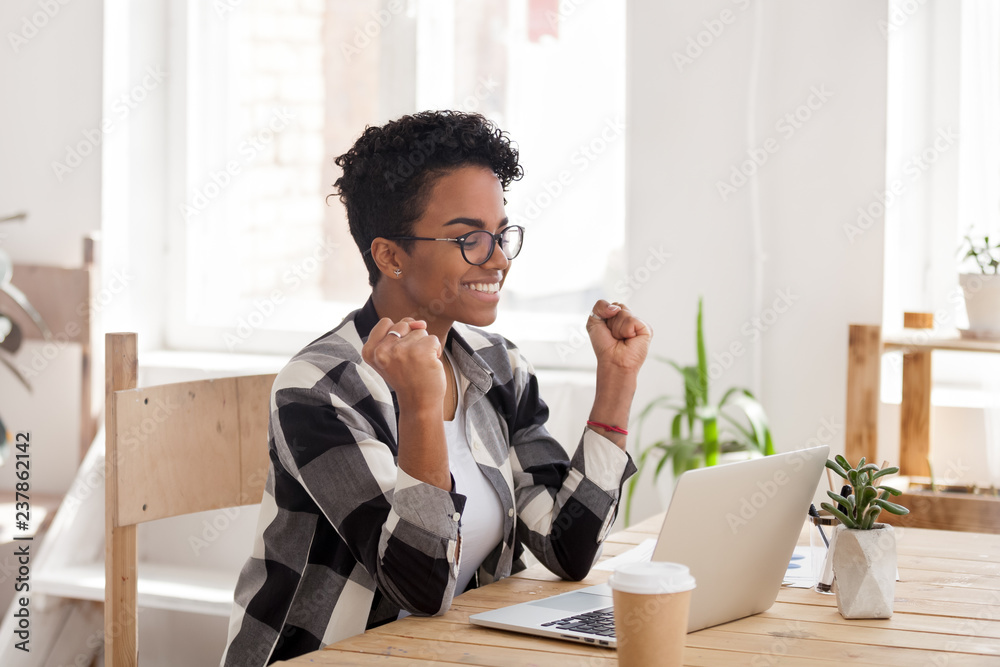 Fototapeta Excited African American woman in glasses read good news online at laptop, happy black female get promotional letter or email celebrating goal achievement, smiling girl look at computer lucky with win