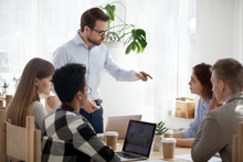 Serious Millennial Businessman Standing Leading Office Meeting Talking To Female Colleague, Male Boss Or Coach Gesturing Scolding Employee Or Worker, Man Mentor Explain Issue To Intern At Training