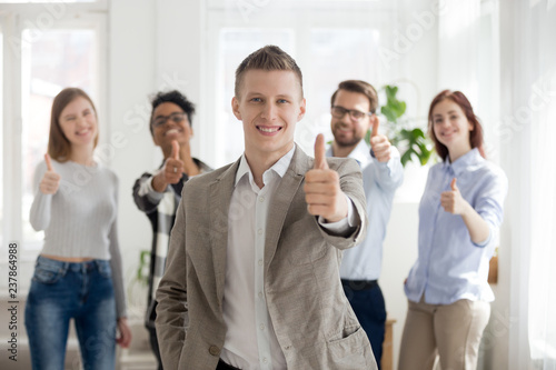 Cuadros en Lienzo Smiling millennial male employee or worker stand foreground showing thumbs up lo