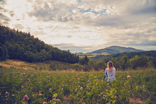 Girl Sitting On A Green Meadow...