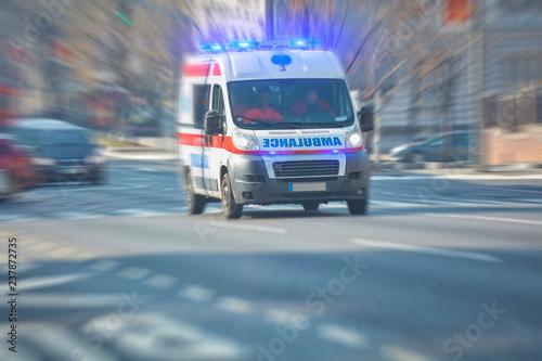 Paramedic 911 ambulance car running fast through the big city. Wallpaper Mural