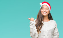 Young Arab Woman Wearing Christmas Hat Over Isolated Background Smiling With Happy Face Looking And Pointing To The Side With Thumb Up.