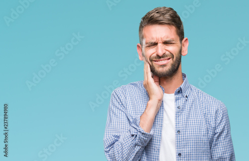 Fotografia  Young handsome man wearing white t-shirt over isolated background touching mouth with hand with painful expression because of toothache or dental illness on teeth