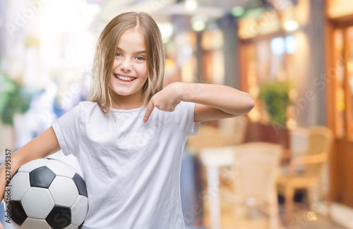 282ad25b3 Young beautiful girl holding soccer football ball over isolated background  with surprise face pointing finger to