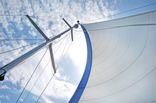 From Below Shot Of White Waving Sail On Tall Mast Under Blue Sky In Clouds . White Sail On Mast Under Blue Sky.