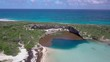Aerial view of Dean's Blue Hole and part of Long Island in the Bahamas. Drone moves forward over sinkhole and green area on island, toward open sea and horizon.