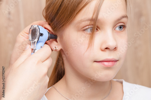 Child ENT check - doctor examining ear of elementary age girl with otoscope Wallpaper Mural