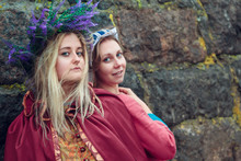 Two Girls In Medieval Reconstruction Costumes With A Handkerchief And A Wreath On Their Heads Posing Near The Stone Wall