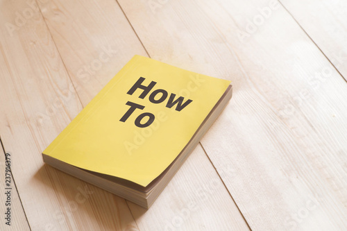 Fotografie, Obraz How to book or guidebook on wooden table