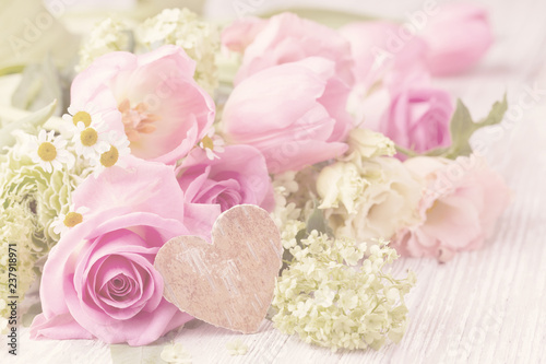 Beautiful spring flowers with wooden heart