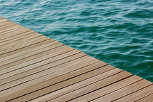 Diagonal Wooden Deck Waterfront Floor Background Texture And Vivid Blue And Green Sea Water Surface With Waves, Copy Space
