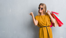 Beautiful Young Woman Over Grunge Grey Wall Holding Shopping Bags On Sales Pointing And Showing With Thumb Up To The Side With Happy Face Smiling
