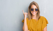 Beautiful Young Woman Standing Over Grunge Grey Wall Wearing Retro Sunglasses Surprised With An Idea Or Question Pointing Finger With Happy Face, Number One
