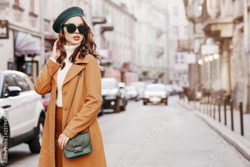 Stampa su Tela Outdoor portrait of young beautiful fashionable woman wearing trendy autumn coat, turtleneck, beret, sunglasses, with small shoulder bag, walking in street of european city