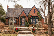 Cute Brick Cottage With Red Bows And Greenery - Decorated For Christmas In Bleak Wintertime
