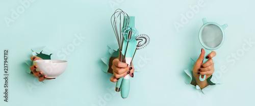 Photo Woman hand holding kitchen utensils on blue background