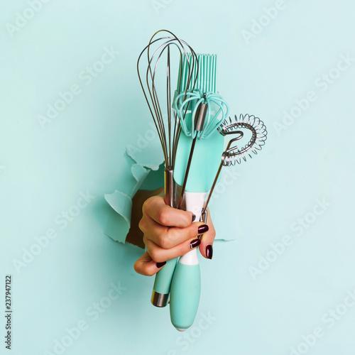 Fototapeta Woman hand holding kitchen utensils on blue background