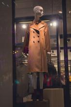 Female Mannequin In Coat In A Shop Window. Sales