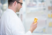 Pharmacist Reading Label On Pi...