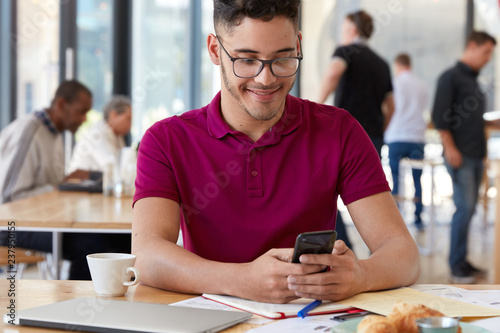 Cropped shot of carefree hipster chats on his smart phone, poses in cozy pub inside, uses free wifi, has cheerful expression, wears casual clothes, sits at desktop with modern laptop, paper documents