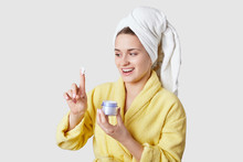 Phot Of Joyful Healthy Female Holds Container With Cream, Satisfied With Its Good Effect, Dressed In Casual Clothes, Bathrobe And Towel, Has Beauty Treatments At Home, Isolated Over White Background